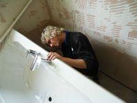 Мастер устанавливает акриловую ванну