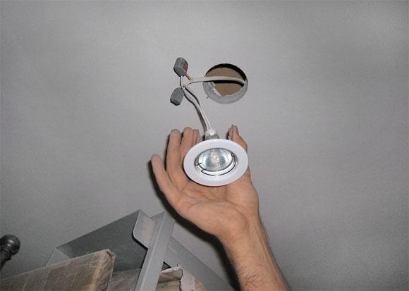 Мастер производит установка светильника на гипсокартон