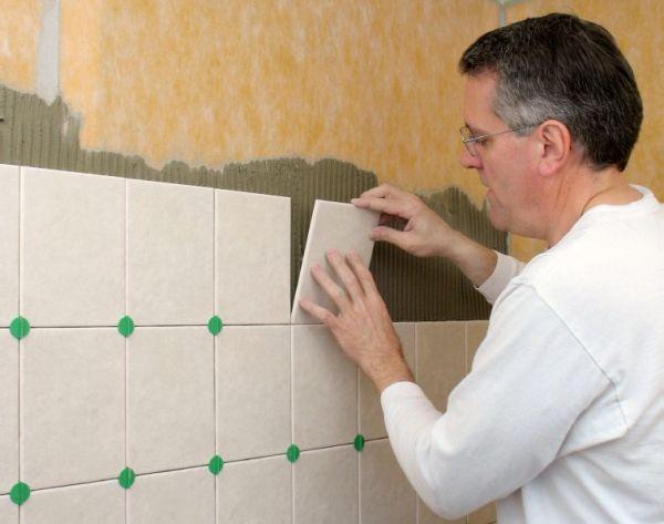 Мастер-плиточник укладывает плитку на стену