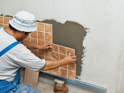 Мастер плиточник кладёт кафель на стену